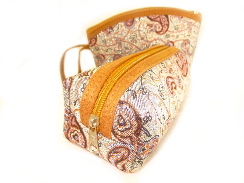 اگر جز افرادی هستید که به دنبال کیف های آرایشی شیک و زیبا هستید. کیف های آرایشی ترمه یکی از بهترین انتخاب هاست.این ست کیف آرایشی از 2 کیف تشکیل شده است.ترمه به کار رفته در این ست،زمینه طلایی وگل های بته جقه ای مشکی و نقره ای قهوه ای روی آن به زیبایی این محصول افزوده است.محفظه داخلیه کیف توسط یه زیپ در بالای آن نمایان می شود.درون این کیف ها آستر کشی شده است.زه های این کیف با نخ های هم رنگ دوخته شده و با رنگ ترمه متضاد و بسیار دل نشین است.اگر به دنبال ست آرایش کوچک و سبک هستید مجله بزرگ این کالا را به شما پیشنهاد می کند.